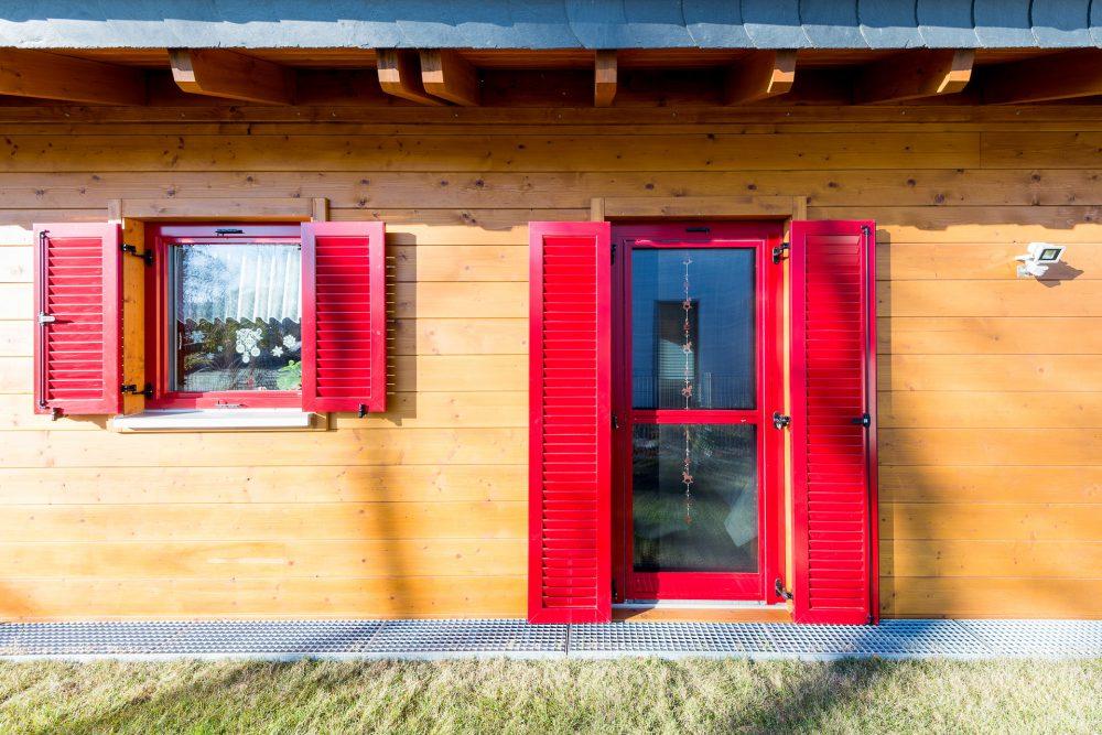 rote Fenster mit Fensterläden im Holzhaus